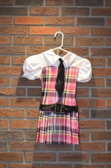For Rent Item 062. School girl costume with yellow and pink plaid, white top with black tie and belt; size: junior.