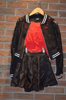 For Rent Item 066. Red shirt with black lace bomber jacket (white trim on wrist and collars), and a black skirt; size: intermediate