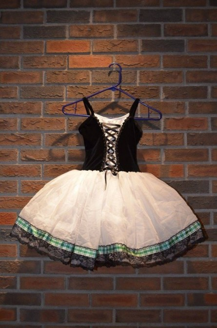 For Rent Item 067. Celtic themed ballet dress, black criss-crossed lacing on top, white tutu with green plaid and lace trim; size: intermediate.